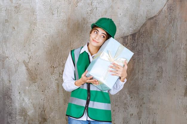 Ingénieur en uniforme vert et casque tenant une boîte-cadeau bleue et semble somnolent et fatigué.