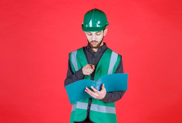 Ingénieur en uniforme vert et casque tenant un dossier bleu, lisant et corrigeant.