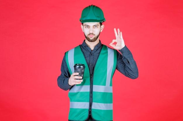 Ingénieur en uniforme vert et casque tenant une tasse de café jetable noire et appréciant le goût.