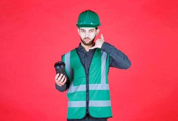 Ingénieur en uniforme vert et casque tenant une tasse de café jetable noire.