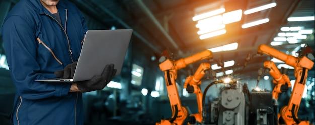 L'ingénieur utilise un logiciel robotique avancé pour contrôler le bras du robot industriel en usine