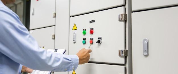 Ingénieur vérifiant le bouton de démarrage de la centrale de traitement d'air sur le système de panneau de commande.