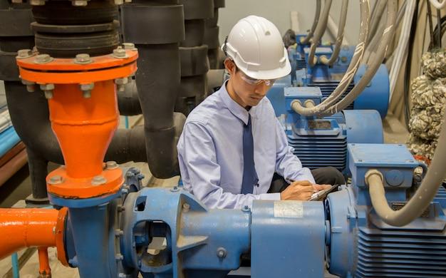 Ingénieur vérifiant la pompe à eau et le manomètre du condenseur, pompe à eau du refroidisseur avec manomètre.