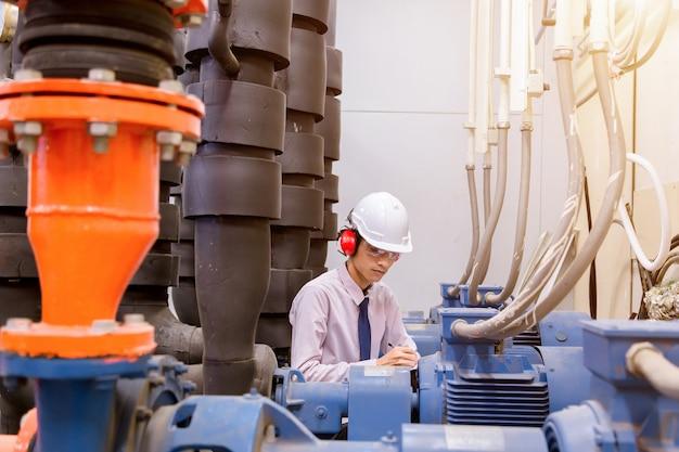 Ingénieur vérifiant la pompe à eau et le manomètre du condenseur.
