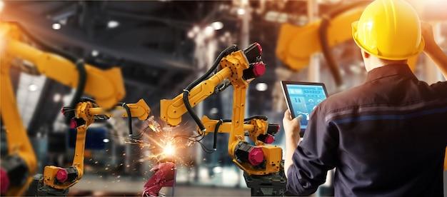 Ingénieur vérifie et contrôle la robotique de soudage machine à bras automatique