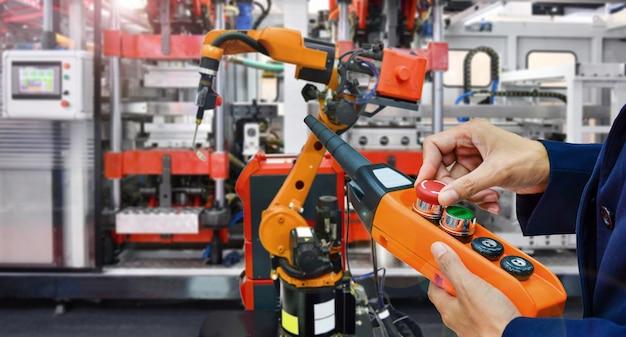 Un ingénieur vérifie et contrôle les robots de soudage automatisés modernes de haute qualité