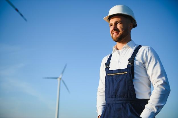 L'ingénieur vérifie la production d'énergie sur l'éolienne. travailleur dans le parc des moulins à vent en casque.