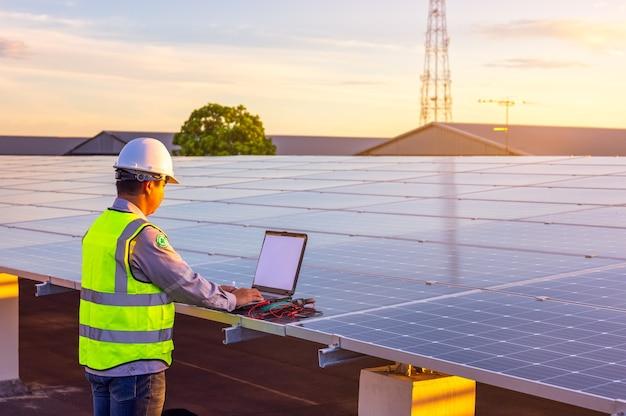 L'ingénieur vérifie le système de centrale photovoltaïque à cellules solaires sur le toit.