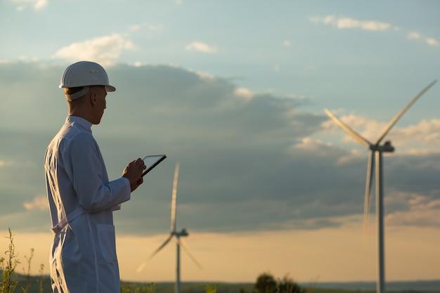 L'ingénieur vérifie le système d'éolienne avec une tablette. énergie alternative. parc éolien. technologies d'énergies renouvelables propres. les centrales éoliennes.
