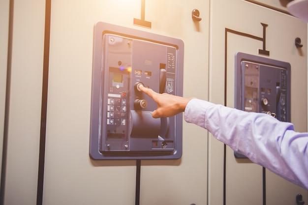 L'ingénieur vérifie la tension ou le courant à l'aide d'un voltmètre dans le panneau de commande de la centrale.