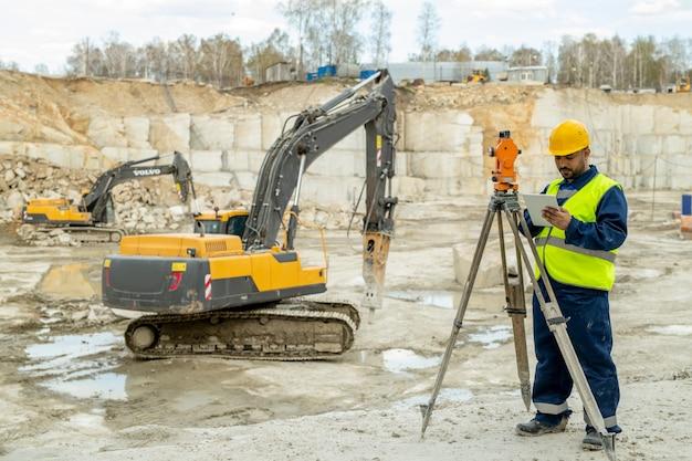 Ingénieur en vêtements de travail debout par station géodésique contre bulldozer