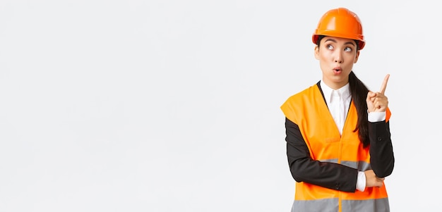 Ingénieure asiatique créative réfléchie, architecte en casque de sécurité et veste réfléchissante, levant l'index, geste eurêka, a une idée intéressante, suggère un plan, a une solution, fond blanc