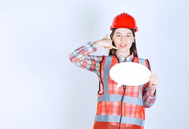Ingénieure en casque rouge tenant un panneau d'information vierge et demandant un appel.