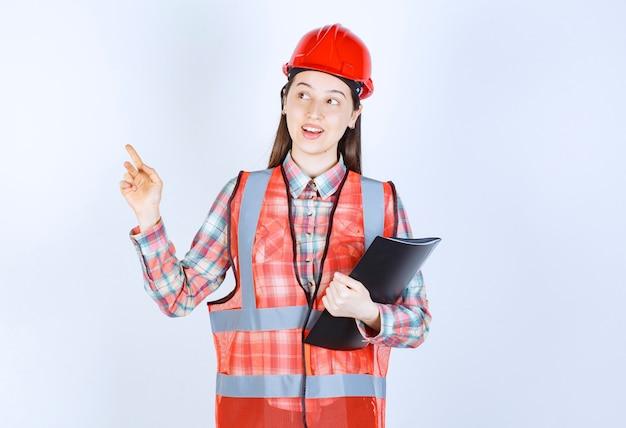 Ingénieure en casque rouge tenant un plan de projet noir et ayant une bonne idée.