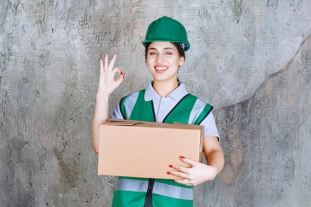 Ingénieure en casque vert tenant une boîte en carton et montrant un signe de satisfaction
