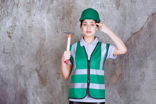 Ingénieure en casque vert tenant une hache à manche en bois pour un travail de réparation, a l'air réfléchie ou a une bonne idée