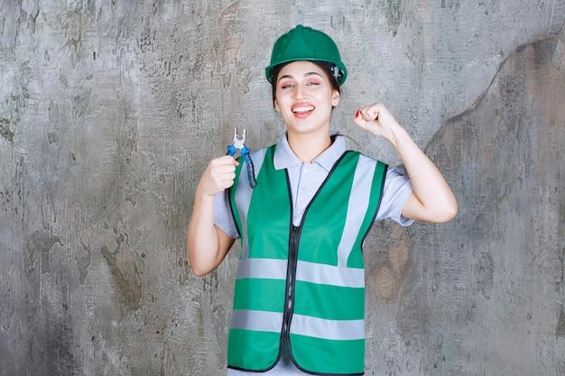 Ingénieure en casque vert tenant des pinces pour un travail de réparation et montrant son poing.