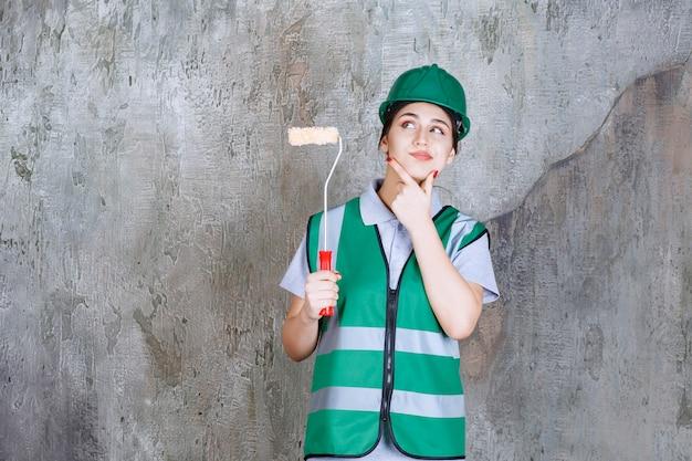 Ingénieure en casque vert tenant un rouleau de finition pour la peinture murale et réfléchissant à de nouvelles méthodes