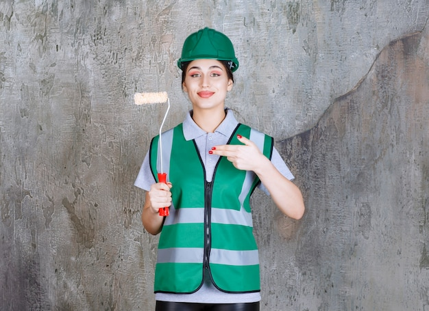 Ingénieure en casque vert tenant un rouleau de finition pour la peinture murale.