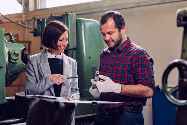 Ingénieure en consultation avec machiniste tenant l'arbre de pignon