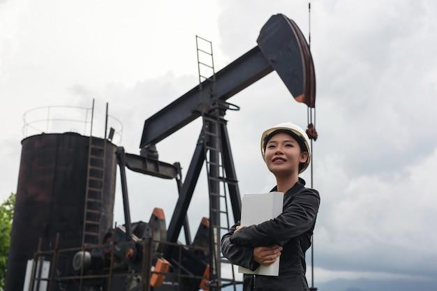 Ingénieure debout à côté de pompes à huile de travail avec un ciel.