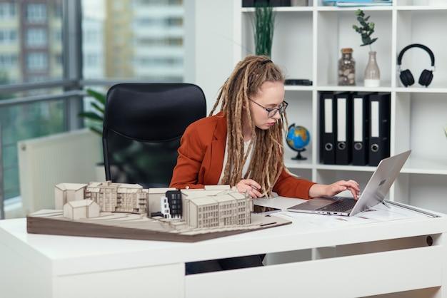 Une ingénieure élégante travaille au bureau d'études avec un ordinateur portable et examine la maquette de la future zone résidentielle.