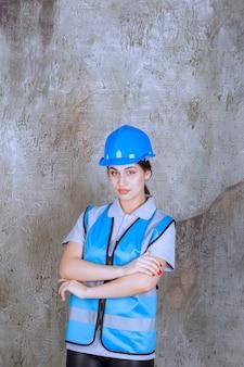 Une ingénieure portant un casque et un équipement bleus et croisant les bras pour donner des poses professionnelles.
