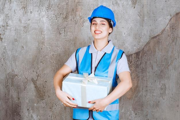 Ingénieure en uniforme bleu et casque tenant une boîte-cadeau bleue.