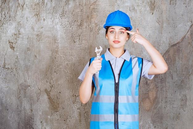 Ingénieure en uniforme bleu et casque tenant une clé métallique et se sentant confuse et réfléchie à la façon de l'utiliser.
