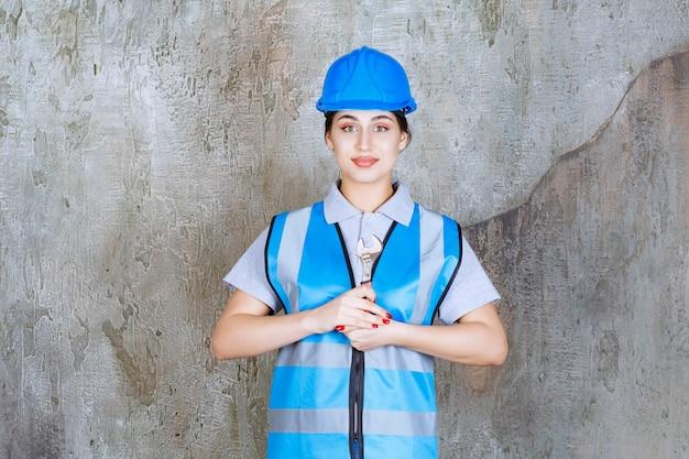Ingénieure en uniforme bleu et casque tenant une clé métallique.