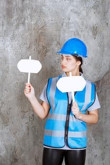 Ingénieure en uniforme bleu et casque tenant deux panneaux d'information vierges dans les deux mains.