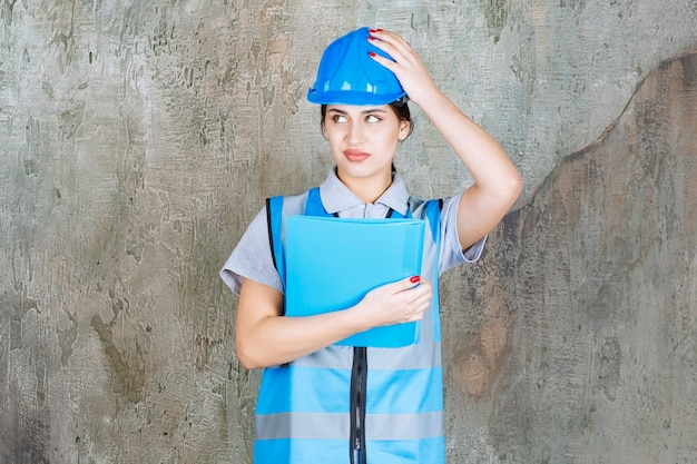 Ingénieure en uniforme bleu et casque tenant un dossier de rapport bleu et a l'air terrifiée et effrayée.