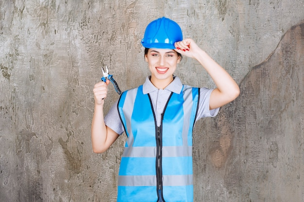 Ingénieure en uniforme bleu et casque tenant une pince métallique pour réparation et montrant un signe positif de la main.