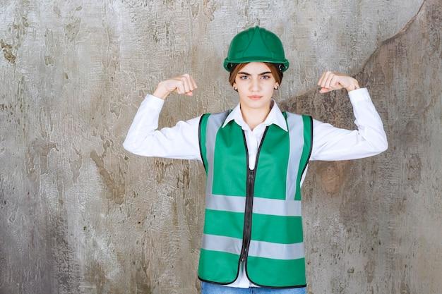 Ingénieure en uniforme vert et casque debout sur un mur de béton et démontrant les muscles de ses bras.
