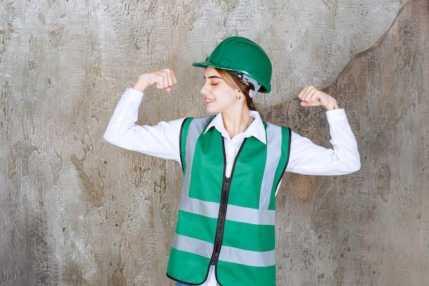 Ingénieure en uniforme vert et casque debout sur un mur en béton et démontrant les muscles de ses bras