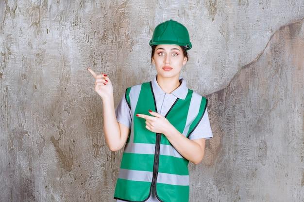 Ingénieure en uniforme vert et casque montrant le côté gauche avec émotions.