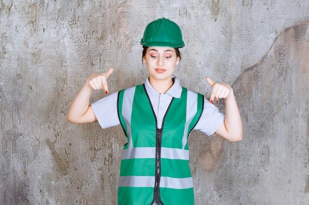 Ingénieure en uniforme vert et casque montrant quelque chose derrière.