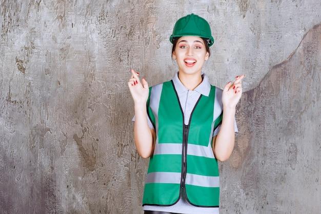 Ingénieure en uniforme vert et casque tenant une croix de doigt.