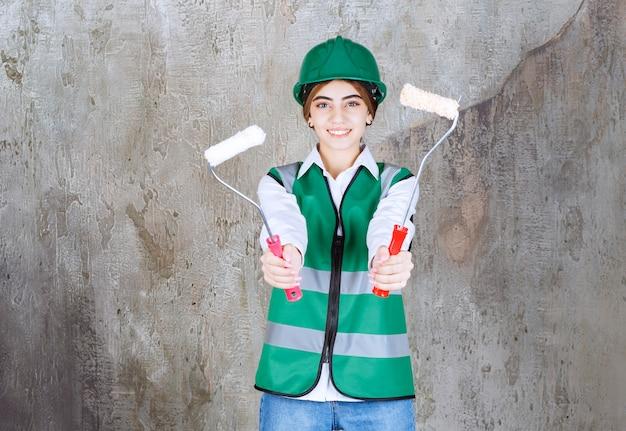 Ingénieure en uniforme vert et casque tenant deux rouleaux de finition pour peindre à deux mains et partager avec son collègue.