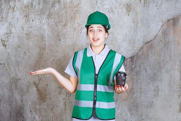 Ingénieure en uniforme vert et casque tenant une tasse de café noir et montrant quelque chose de côté.