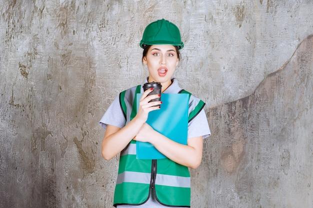 Ingénieure en uniforme vert et casque tenant une tasse de café noire et un dossier de projet bleu