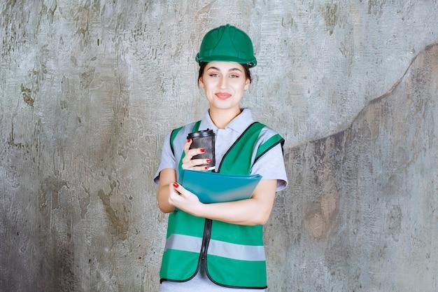 Ingénieure en uniforme vert et casque tenant une tasse de café noire et un dossier de projet bleu.