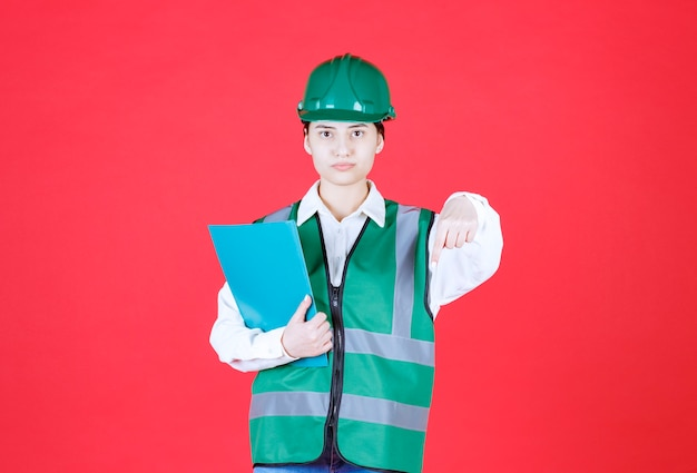 Ingénieure en uniforme vert tenant un dossier bleu et appelant son collègue