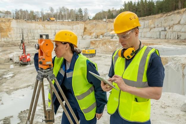 Ingénieure utilisant la station géodésique pendant que son collègue fait défiler la tablette