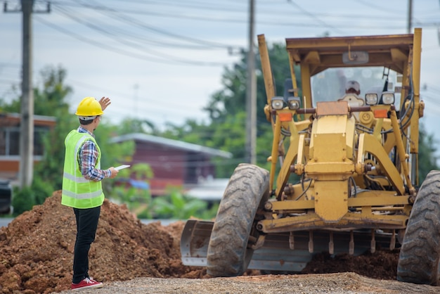 Des ingénieurs asiatiques regardent la reconstruction de la route et inspectent la construction de la route sur le chantier.