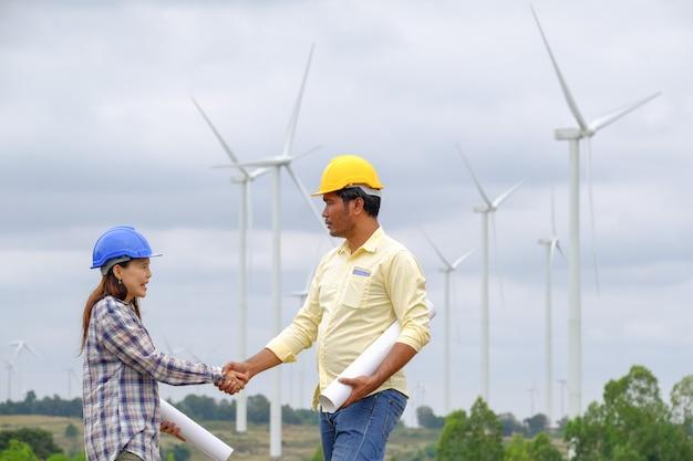 Des ingénieurs asiatiques de sexe masculin et féminin envisagent de développer l'énergie éolienne.