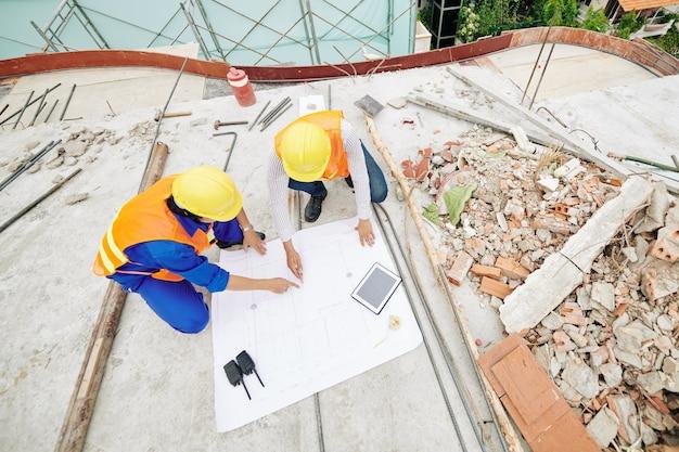Ingénieurs civils pointant sur le plan du bâtiment et discuter des détails, vue d'en haut