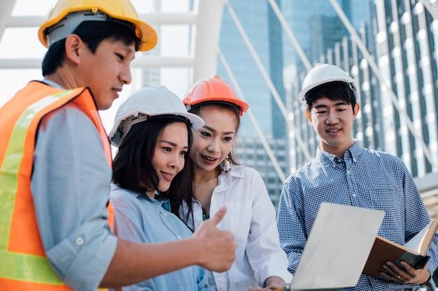 Ingénieurs et collègue regardant un ordinateur portable. concept de travail d'équipe.