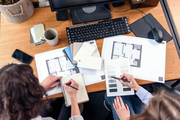 Des ingénieurs de conception féminins discutent d'un projet et apportent une correction finale à la couleur au bureau. vue de dessus.