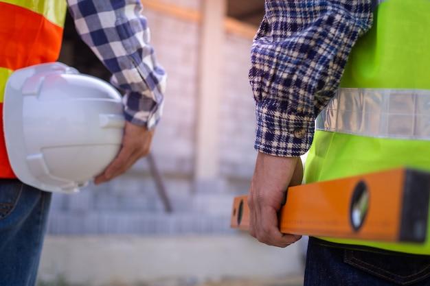 Ingénieurs et constructeurs professionnels en vêtements de travail avec des outils et tenant des casques blancs tout en se tenant à l'extérieur du chantier de construction.